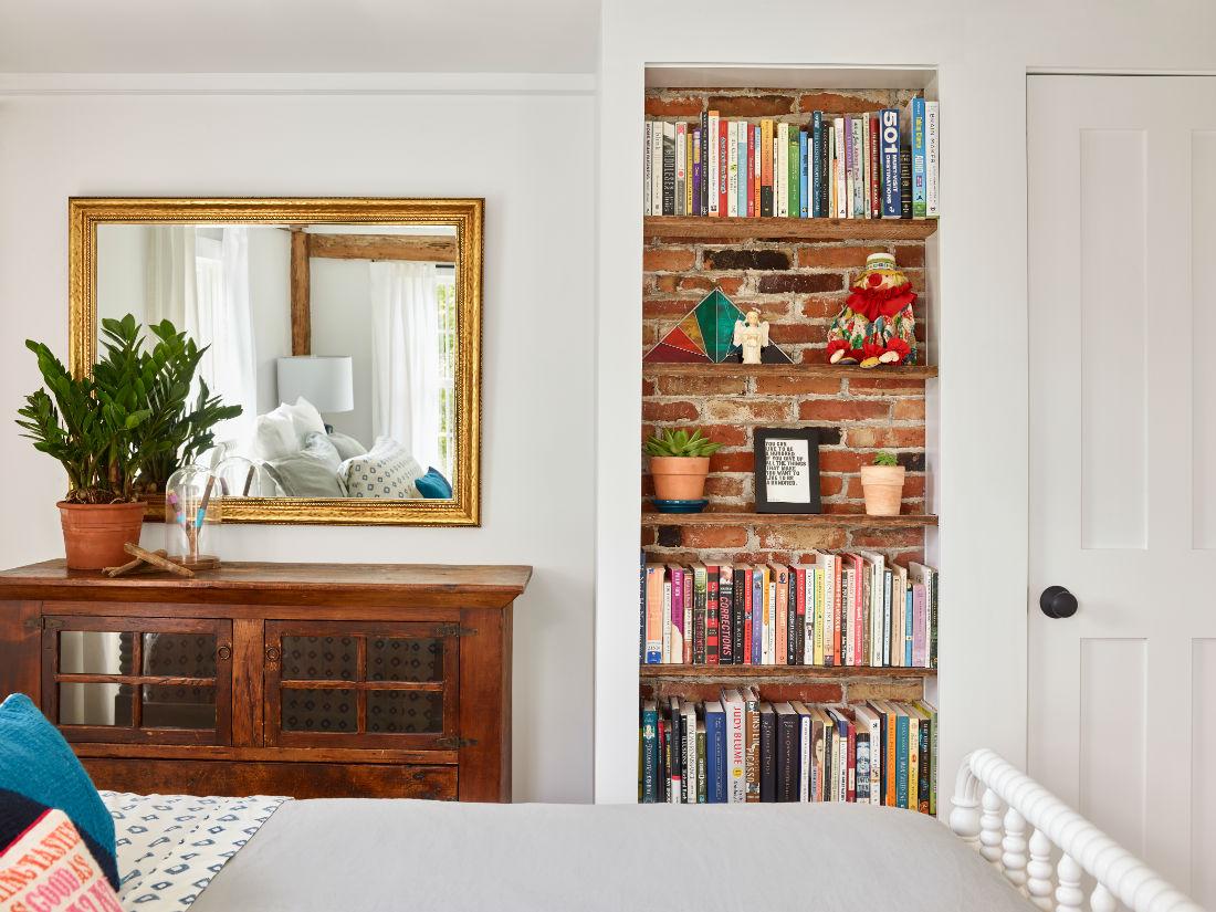gues-bedroom-exposed-brick-behind-book-shelf